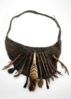 Sling bag with hunting trophies, made of braided plant fiber and decorated with bird legs and upper beak of a cassowary bird | From Savarape, Meervlakte, Papua.  Collected in 1926