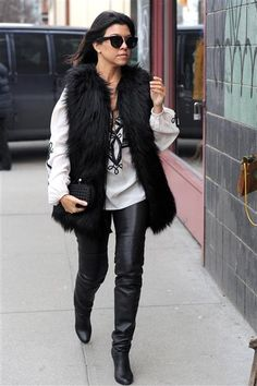 Kourtney Kardashian in a furry vest, leather leggings and thigh-high boots