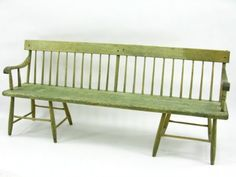 Measures 31 x 72 x 14.5 x 15.5 inches. Reamining old green finish, spindled back, carved wood arms, interesting dual chair bases each end with eight reinforced legs.