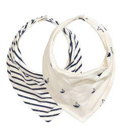 Fodrade trekantsscarves i mjuk bomullstrikå. Reglerbar knäppning med tryckknappar i nacken.