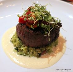 Filet mignon on bed of bacon risotto and parmesan butter sauce, topped with roasted tomatoes and microgreens.