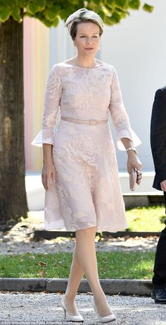 Queen Mathilde of Belgium wore a pink floral embroidered dress which fell to the knee. Flared sleeves provided a quirky touch, exposing a delicate watch as she clutched a neat handbag and a pair of gloves. She topped off her look with a f Princess Letizia, Estilo Real, Royal Look, Church Outfits, Family Outfits, Royal Fashion, Women's Fashion Dresses, Mother Of The Bride, African Fashion