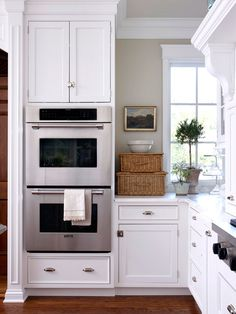 Lovely stacked baskets add additional storage to a kitchen countertop without looking cluttered.