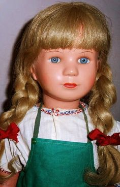 """16"""" celluloid girl doll in factory original clothes, with blonde human hair wig and inset eyes, wearing a classic Bavarian girls' apron-pinafore, designed by Käthe Kruse, West Germany, 1950-55, by Schildkröt."""