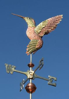 The Anna's Hummingbird Weathervane is handmade from brass and copper with a custom-made blue glass eye and optional gold leafing. Personalization available.
