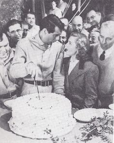 "Cary Grant slices a birthday cake presented to him on the set of ""Only Angels Have Wings"". On his left is Jean Arthur"