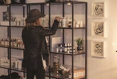 <p>Across from the stations, co-owner Alexandra Elman tests different lotions and creams. The retail case holds a large selection of natural beauty products. To the right is art from a local artist, Strange Dirt.</p>