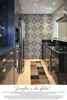 cozinha sofisticada - armários em azul marinho e puxadores dourados, cores que se repetem no revestimento da parede ao fundo