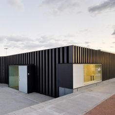 These ridged metal walls enclose the facilities of an outdoor swimming pool that Spanish firm Arquitecturia have just completed in the town of Tortosa.