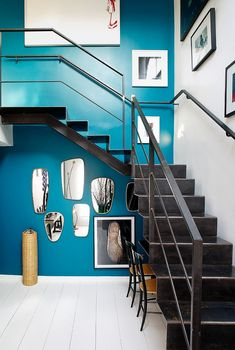 Curated mirror display under the staircase [Design: Sarah Lavoine - Studio d'architecture d'intérieur]