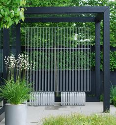 We will have a dark grey pergola similar to this, built in Top Garden, near to large laurel, paved beneath to give contemporary look.