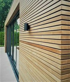 An outbuilding finished with thermo ash wood cladding and black sliding . - An outbuilding finished with thermo ash wood façade cladding and black sliding doors for optimum u - Wooden Wall Cladding, Larch Cladding, House Cladding, Wood Facade, Exterior Cladding, Facade House, Wooden Walls, House Facades, Family Room Walls