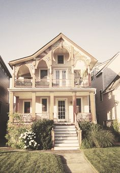 Love the second story porch with the gingerbread trim.
