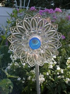 Glass Flower....  One large plate,  one small plate,  and one candle holder.  Glue it together.    Then I glued a thing called a bell hanger  - it's in the plumbing section -  to the back of the big plate.  I then attached a 3/4 in pipe to the bell hanger.  And then I planted it!
