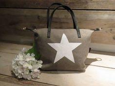 Leuke stoere handtas met riem, zodat deze ook als schoudertas te dragen is.  Kleur: Taupe met witte ster  Afmetingen  Lengte: 29cm Breedte: 13cm Hoogte: 22cm