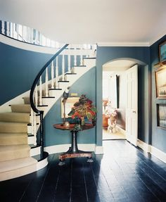 Design Ideas: Dark Foyer In Blue With A Staircase. curved stairway. dark wood flooring. classic round table. gray foyer.