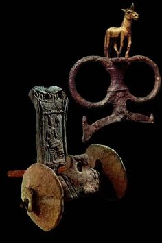 Model of a two-wheeled Sumerian chariot, with chariot rein post and rings. The model of the chariot shows the image of a god on its interior.panel.It is from a later period (Neo-sumerian,ca 2000 BC)