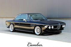 Ik wil een BMW E9. Zwart metallic met zwarte lederen kuipzetels en een houten stuurwiel.
