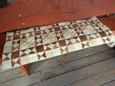Here is a batik table runner in warm shades of brown and cream. The top patchwork blocks are done in batik fabrics. The reverse side is a bow pattern on a brown background. This reversible table runner offers two different looks in one. A matching companion table runner in a smaller