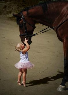 Little girl giving a horse a kiss. :-)