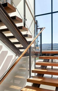 Steel and wood stairs with a glass handrail lead up to the second floor of this modern house. Glass Handrail, Wood Handrail, Glass Stairs, Home Stairs Design, Railing Design, House Design, Steel Stairs, Wood Stairs, House Staircase