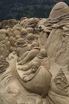 Sand sculpture: canoe, filled with people, going down a river