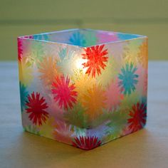 such a great idea for a candle.  punch out tissue paper into flowers, modge podge onto a dollar store vase.