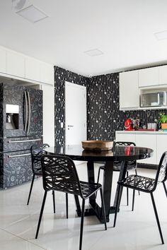 Cozinha   Apesar de branco, o planejado da Elgin, inserido no projeto, sobressai no ambiente, que foi revestido de papel de parede da Ville Marie. Para fugir do comum, a geladeira recebeu película adesiva. Mesa e cadeiras da LZ Studio (Foto: MCA Estúdio)