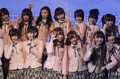 Members of SNH48, a Shanghai-based Chinese girls group, pose for photographers during a press conference before performing their first stage on Saturday, Jan. 12, 2013 in Shanghai, China. They are newly-launched sister group of Tokyo-based AKB48.