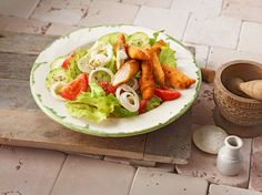 Schnitzelstreifen auf gemischtem Salat mit Tomaten