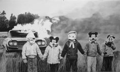 """I have no idea what this photo is about but I love photos like this. That's gotta be one hell of a story behind it. Or maybe it's just, """"Let's set a car on fire, stand in front of it holding hands wearing disney character masks and snap a photo."""""""