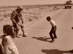 U.S. Army Capt. Michael Findlay plays soccer with an Iraqi child in the suburbs of Kirkuk, Iraq, this past fall. Findlay helped set up stuffed animal and soccer ball donations for children overseas through his parents here. The soldier, who recently returned home, is now working with another unit to continue the program in Afghanistan.