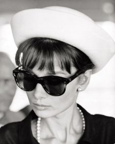 The actress Audrey Hepburn photographed by Pierluigi Praturlon at the Orly Airport, before her trip to Taormina (Italy). Paris (France), July 28, 1962. Audrey was wearing: Dress: Yves Saint Laurent (black, of silk linen, sleeveless, of his collection for the Spring/Summer of 1962). Pearl necklace: Bvlgari. Hat: Givenchy (lined with white felt, of his haute couture collection for Spring of 1962). Sunglasses: Oliver Goldsmith (created especially for Audrey in 1956. The same that she wore in…