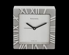 Tiffany & Co. Travel Clock~ This stylish Atlas travel clock was crafted by the celebrated luxury firm Tiffany & Co. The timepiece is housed in a square rhodium frame that is adorned by bold Roman numerals, allowing one to easily tell the time. A Swiss quartz movement powers the clock, which also boasts an alarm function, enhancing the functionality of this truly exceptional timepiece. ~M.S. Rau Classic Clocks, Mantel Clocks, Antique Clocks, Telling Time, Roman Numerals, Get Directions, Quality Time, Free Gifts, Tiffany