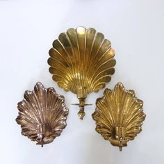 A set of three solid brass vintage shell candle sconces. These beautiful sconces have a wonderful Hollywood Regency look!  The sconces are made of heavy brass. They have a scalloped shell shape with lovely patina. Two of the sconces are the same design and one is different. They each have different patina.  They in very good vintage condition. There are some minor discoloration spots which could be polished out if desired.  Measurements: smaller 8 x 7 x 1.5; larger 11 x 9 x 4.5  Stop by my…