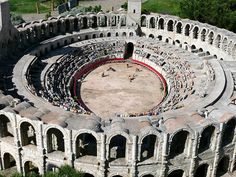 The Roman amphitheater at Arles, France, which dates from 90 AD. It was capable of seating over 20,000 spectators, and was built to provide entertainment in the form of chariot races and bloody hand-to-hand battles.  It is the site of bloody bull-fights today.