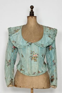 c. 1790 silk jacket; closes in the front by six hooks, covered by a placket; sleeves close with one fabric-covered button. A peplum, pleated in the back, is attached to the bottom. Boned with baleen, lined with linen, collar, peplum and placket lined with waxed canvas. Severočeské muzeum v Liberci, T05316.
