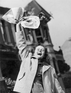 Mrs Pat Burgess of Palmers Green, North London waves a newspaper containing the news of Germany's surrender in WW II. She hopes this means that her husband will soon be home for good from Germany.