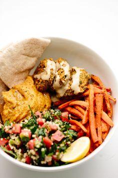 Pumpkin-lentil falafel, millet tabbouleh, pumpkin hummus, roasted cumin carrots, and warm pita bread.