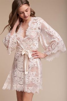 Cinched with a satin sash, this antique-inspired, blush-hued lace robe is the epitome of romance. We fell in love with its feminine details, namely its scalloped sleeves and eyelash trim.