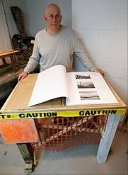 """Professional photographer Larry Racioppo created this library stand from scrap lumber, yellow """"caution"""" tape and orange plastic construction fencing to display his personal photo album showing the destruction in the Belle Harbor section of the Rockaways in New York. The album is among 200 photographs on display in the exhibit """"Rising Waters: Photographs of Sandy,"""" which opens at the Museum of the City of New York on Tuesday, Oct. 29."""