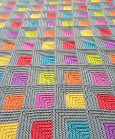 This is a nice blanket, great design. It's mitered, its colorful! I love how colors play off gray. It looks like my diamond dishcloths without the loop, perhaps it is made the same way. The pattern is