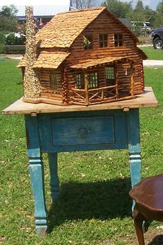 "A handmade ""Adirondack log cabin"" dollhouse. I own one too, in my Adirondack cabin. I like the stone chimney and twig railings on this doll house."