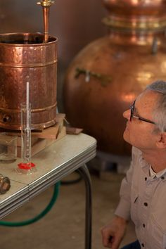 Chuck Morris uses a precision hydrometer to measure the alcohol content in a batch of spirits.  *Copper pot still made by Hoga Company