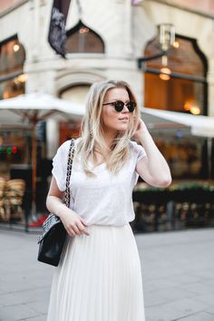 Linda Juhola in white and black. Ray Ban Clubround sunglasses and Chanel bag