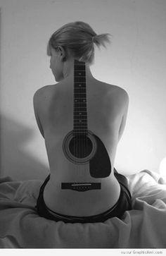 Une guitare en tatouage dans le dos d'une femme.