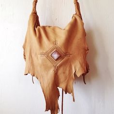 ・Hand crafted carry-all cross-body bag in tobacco colored deerskin. Features a raw edge front flap with an inset rose quartz pyramid and hand burned design , a round 4-part braided strap, whip stitching and hand sewn construction. Interior pocket will hold essentials, such as an iPhone. An original Three Arrows leather hand burned design surrounds the bag and is on the back.・Additional colors of hides available. See the drop down menu below.* The top of the strap is flat for s...