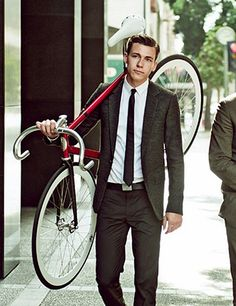 He's carrying a bicycle...and is wearing a suit and looks purrty darn good doing it.