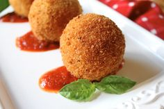 Arancini : fried rice balls coated with breadcrumbs, said to have originated in Sicily in the 10th century. Arancini are usually filled with ragù (meat sauce), tomato sauce, mozzarella, and/or peas.