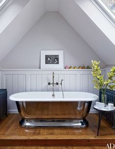 An Henri Cartier-Bresson photograph overlooks the master bath's Water Monopoly tub at a London penthouse designed by Veere Grenney | archdigest.com